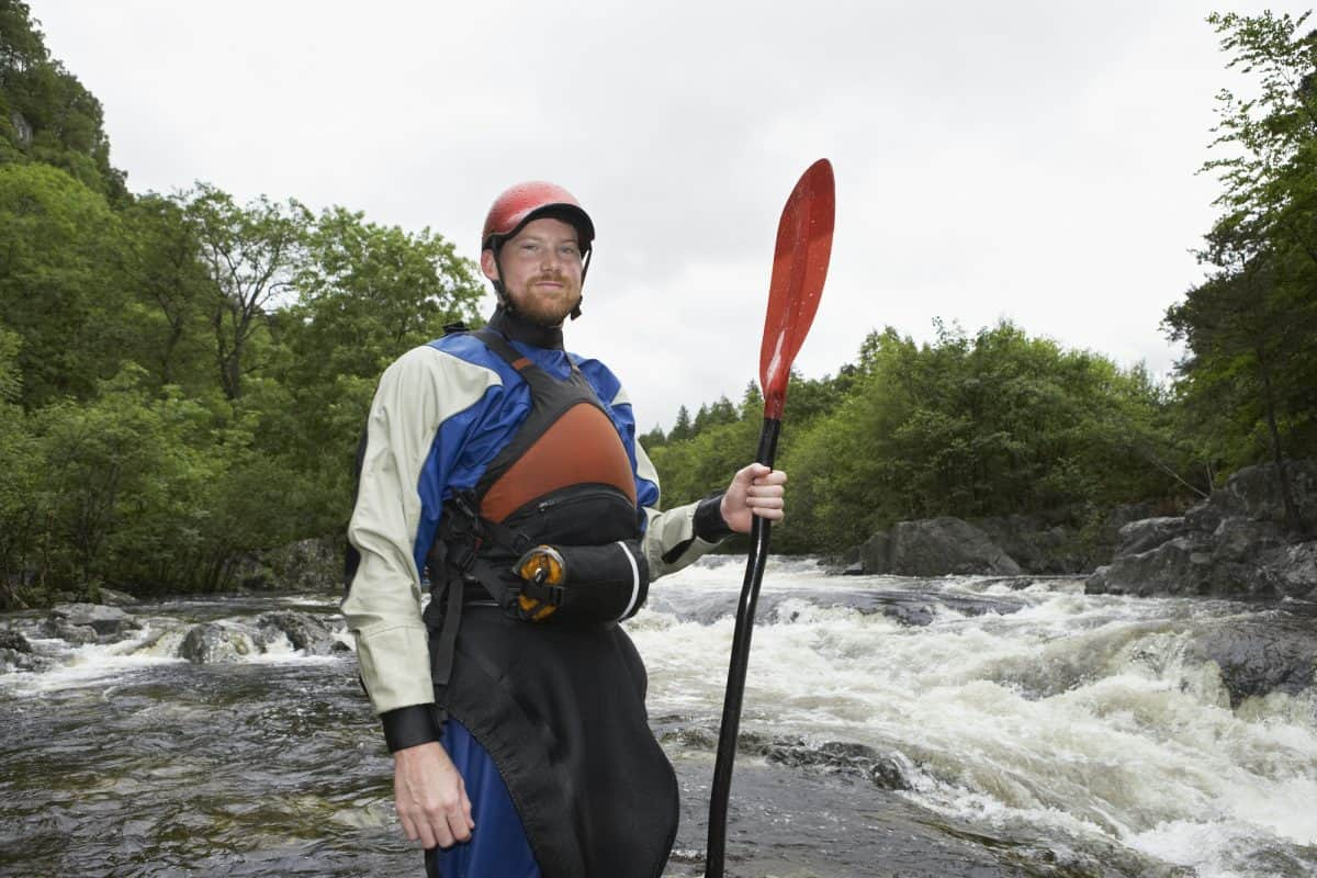 Man in dry suit demonstrating whitewater kayaking gear