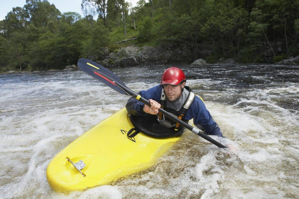 man edges whitewater kayak through rapids