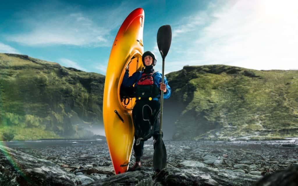 Man poses at water edge hilding yellow kayak, dressed in drysuit and waterwater kayak