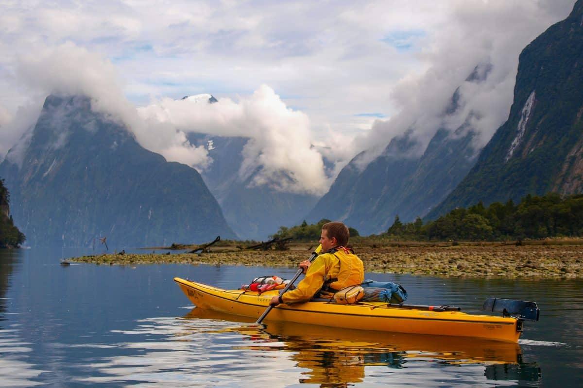 Man in yellow touring kayak on open lake