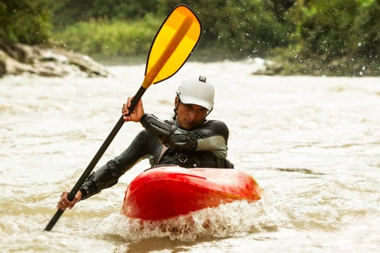 Whitewater kayaker in full gear holding yellow paddle