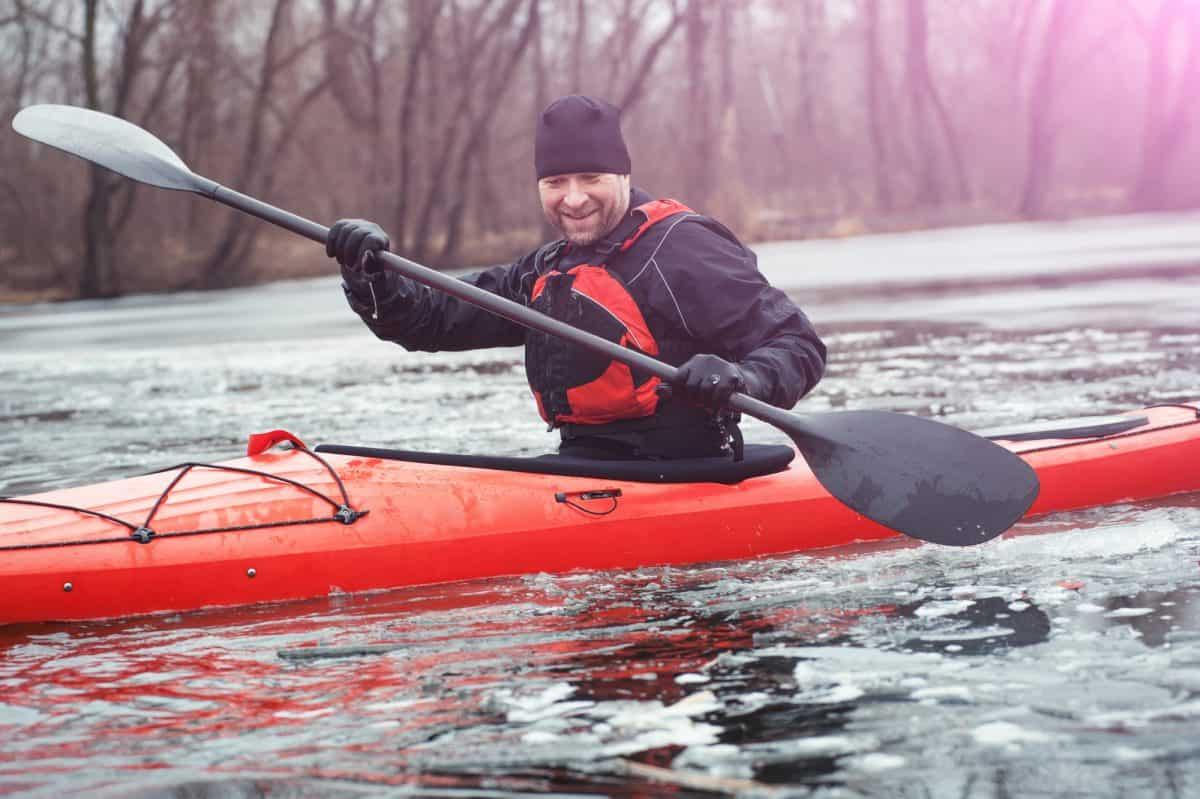 Cheerful Man in drysuit paddling orange kayak