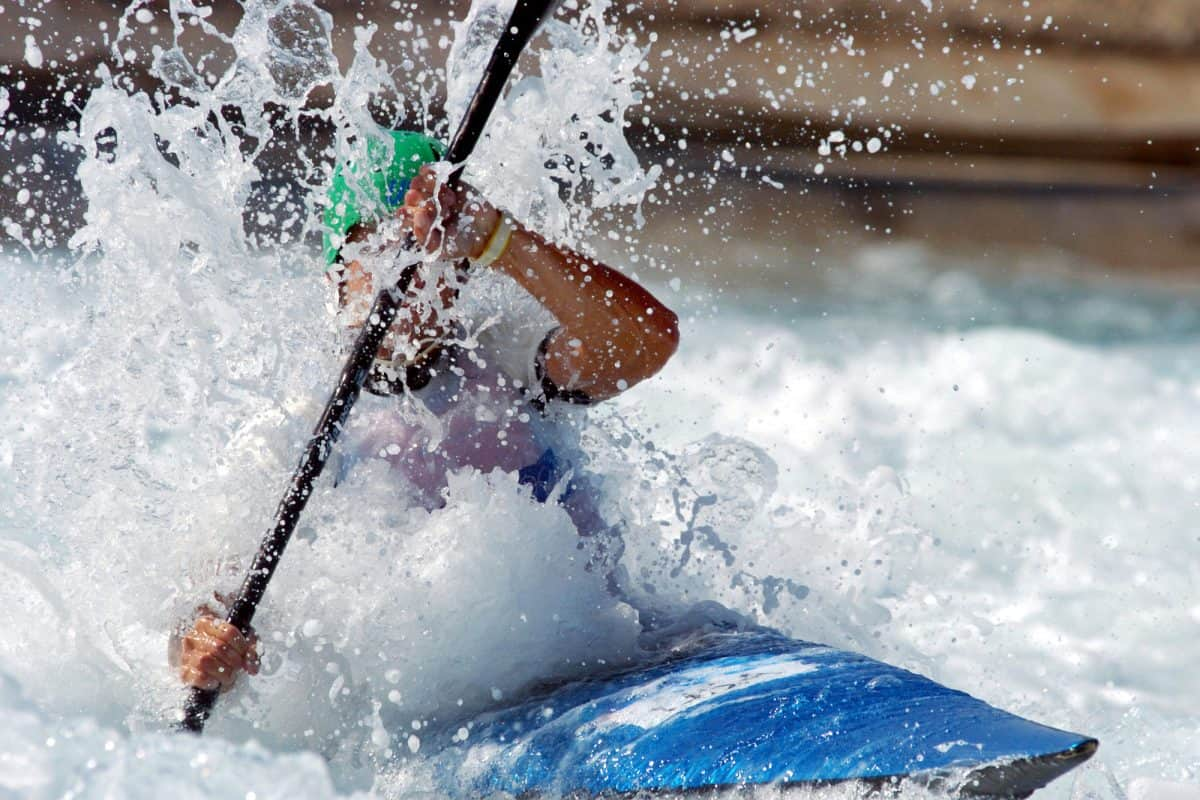 Man paddling through the foam of the whitewater in blue playboat