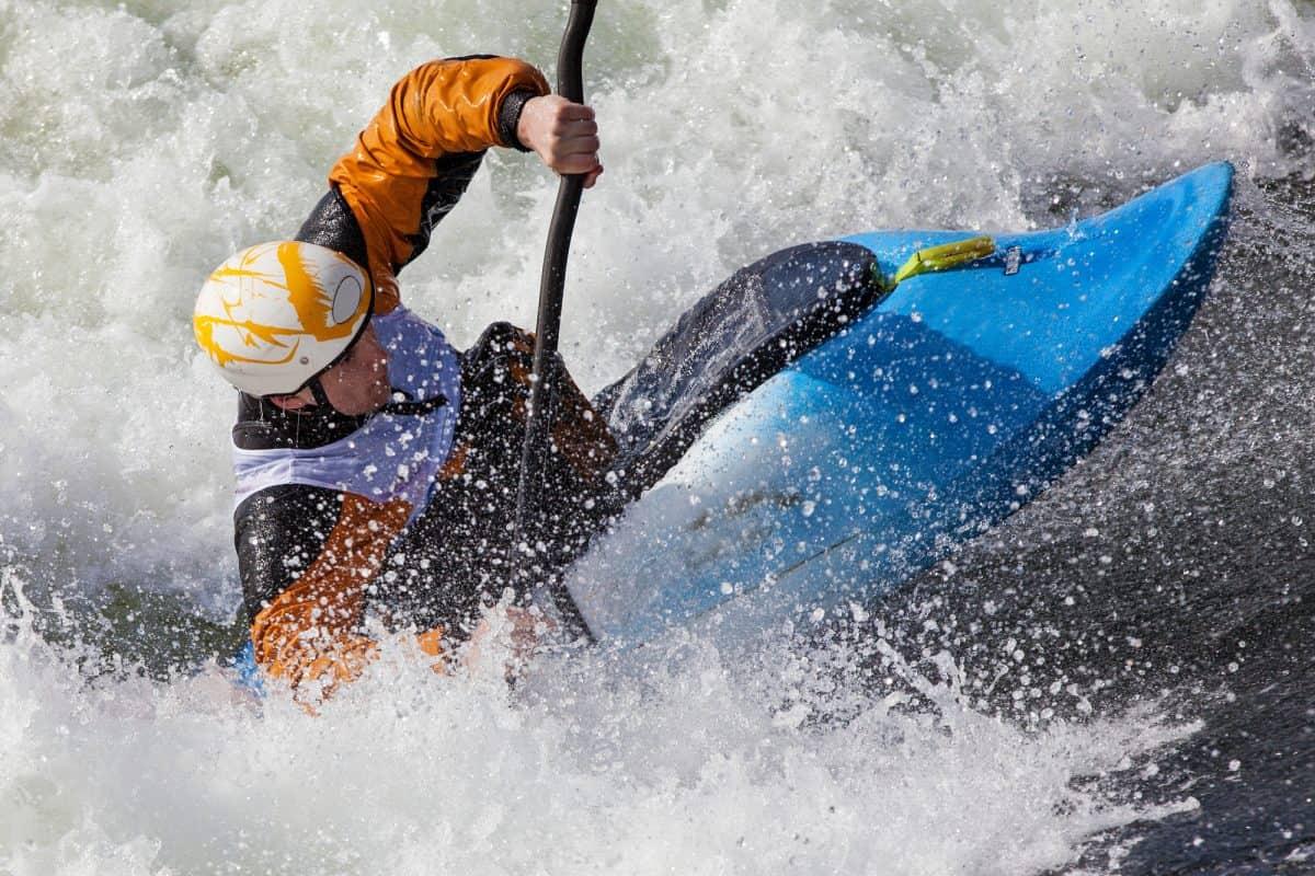 Man in blue whitewater kayak and Orange drysuit