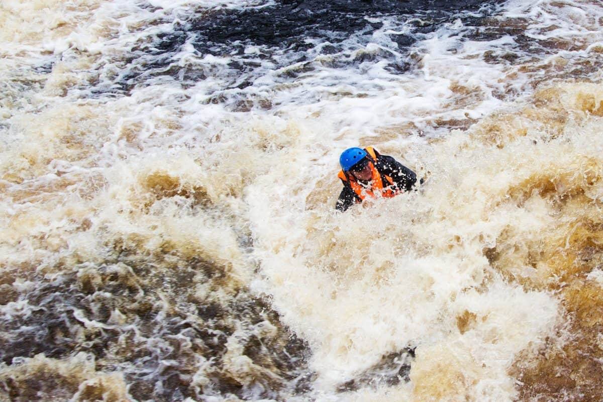 Person in life jackets drowning in a turbulent river