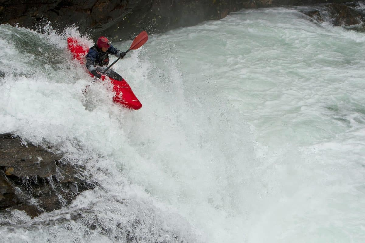 Man dropping from waterfall in red whitewater kayak