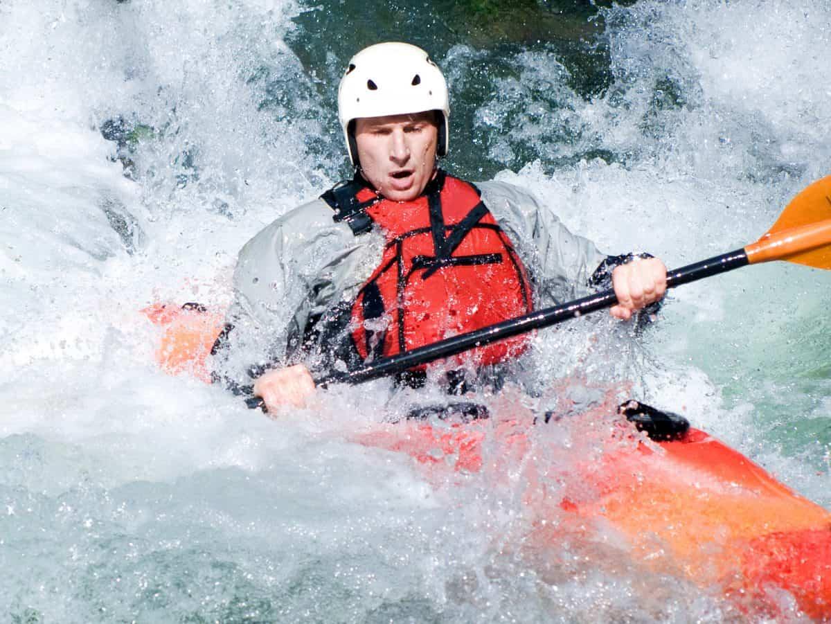Man in orange kayak being swapped by rapids