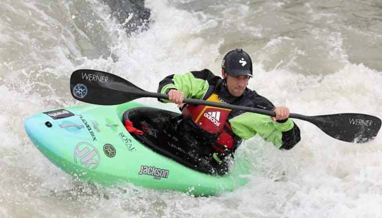 man fights whitewater rapids in green playboat