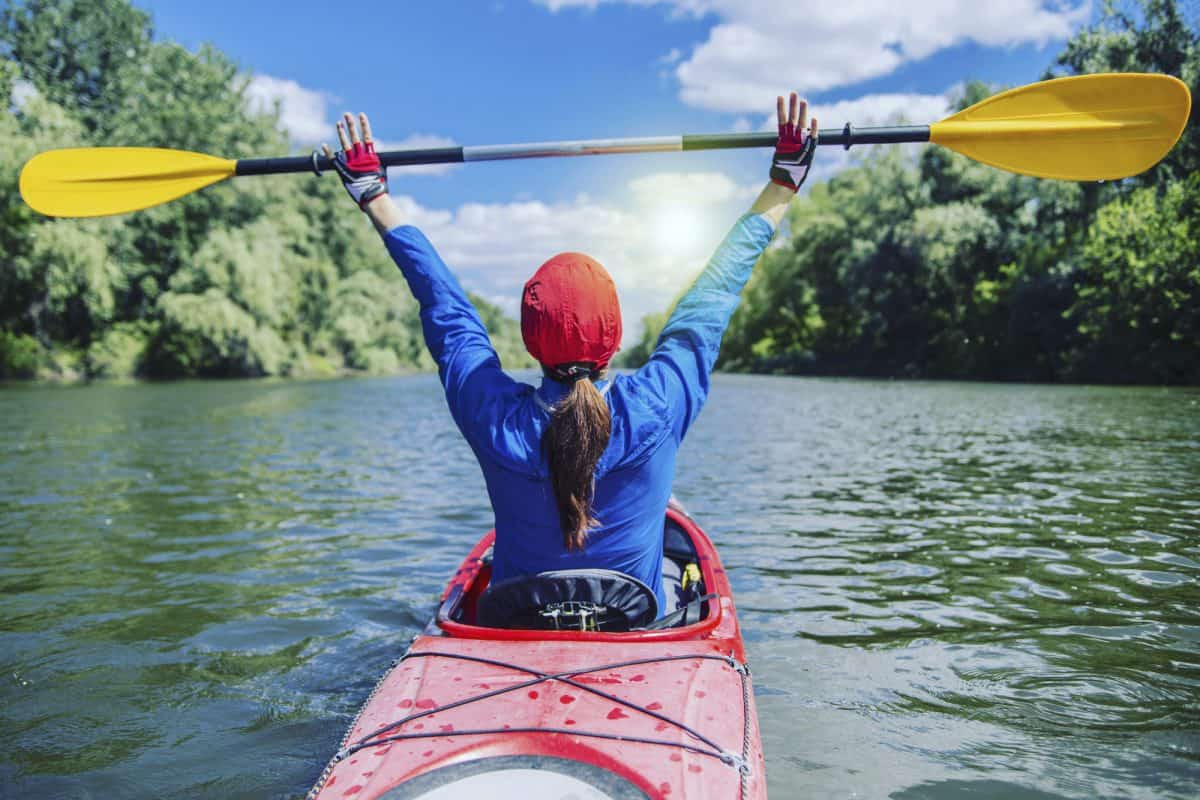 A girl paddles a red kayak on a river in a sunny day