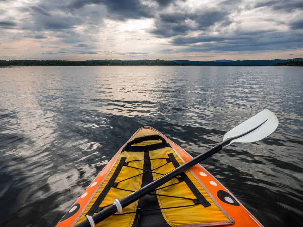 Point of view shot from inside kayak with paddle laying on deck on lake