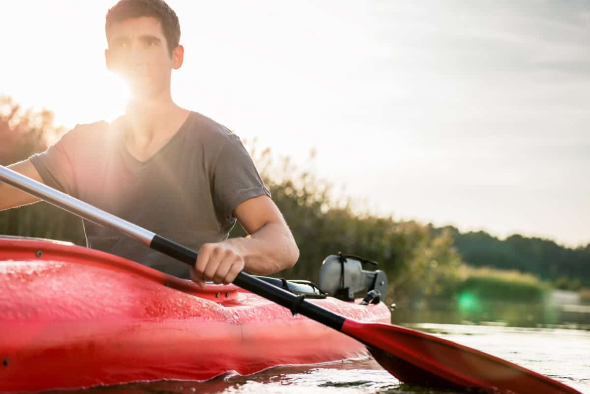 Man with red paddle kayaking in sunny day on lake