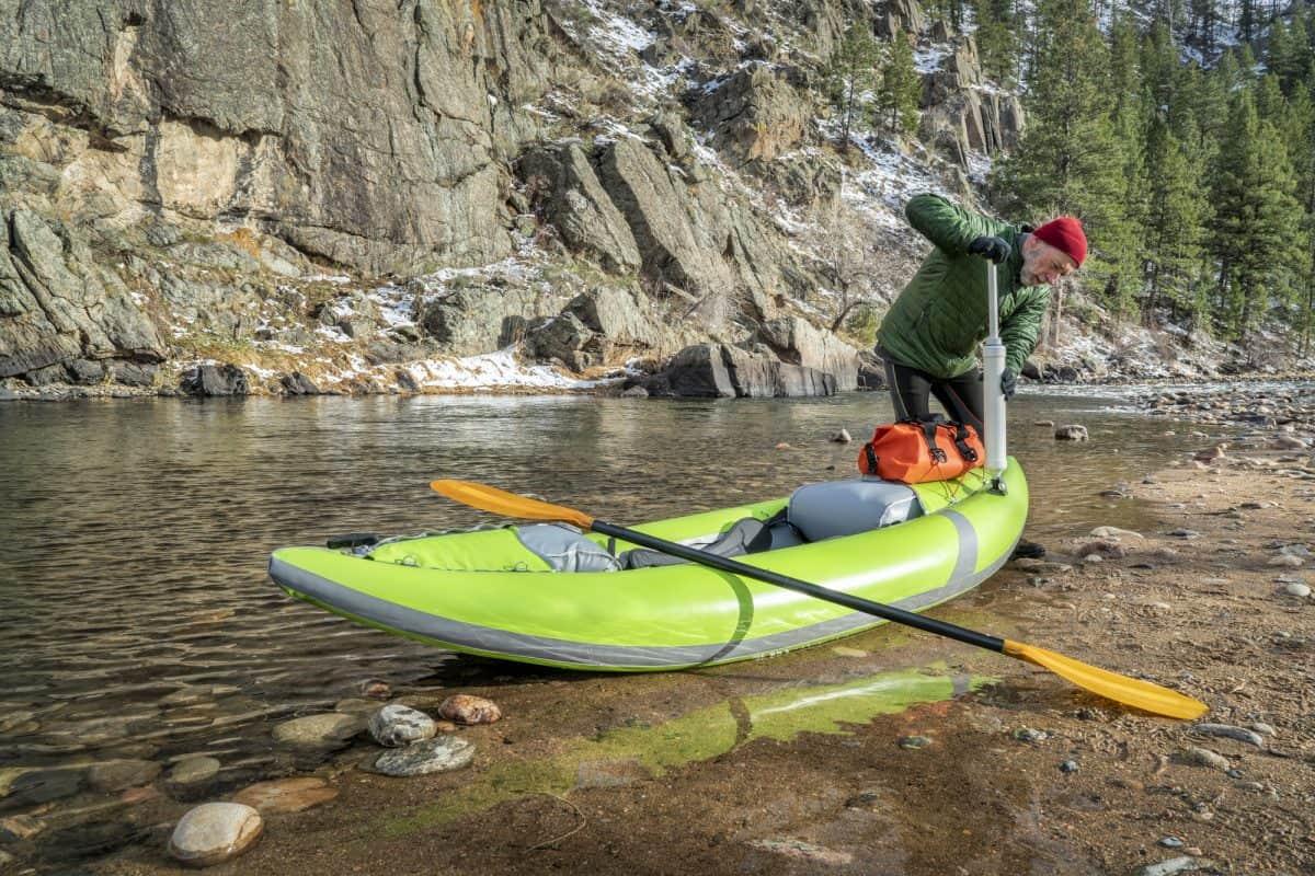 Paddler pumping up inflatable whitewater kayak