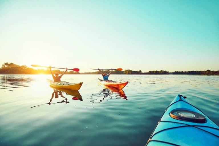 three kayak on the water at sunset