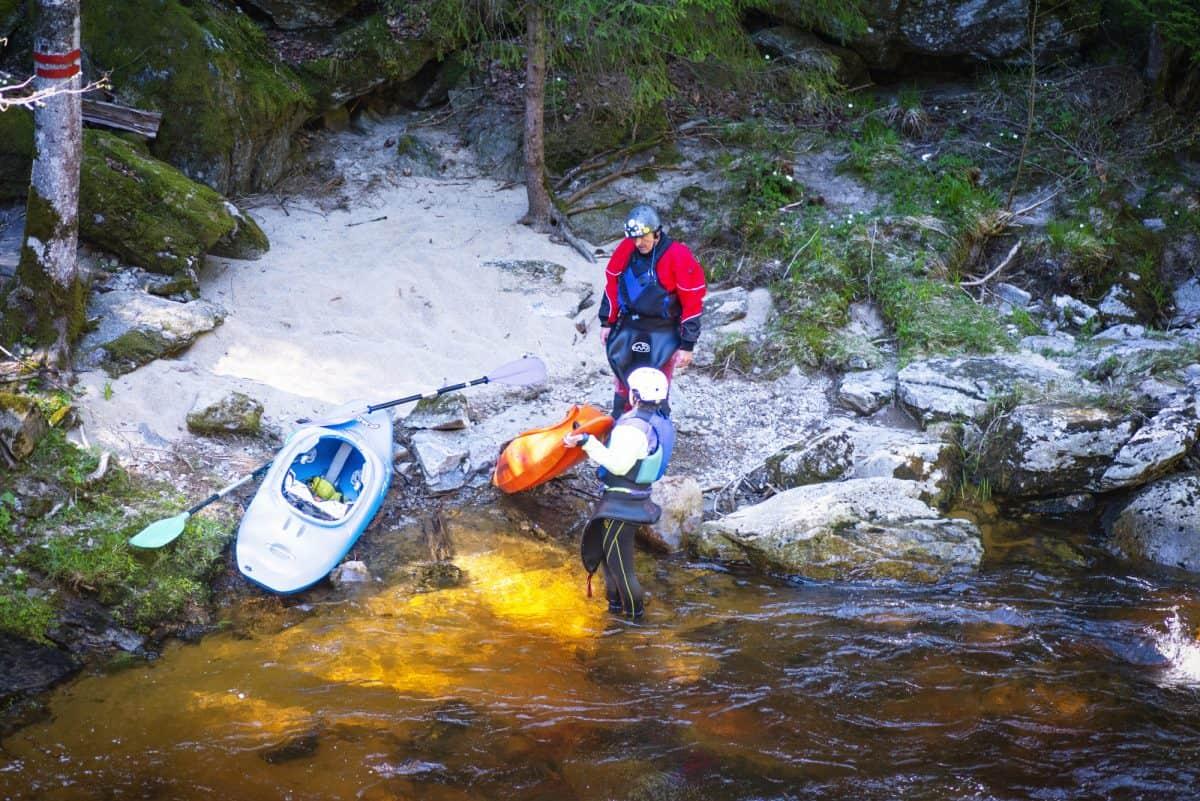 Man and women on river bank, portering around river hazards