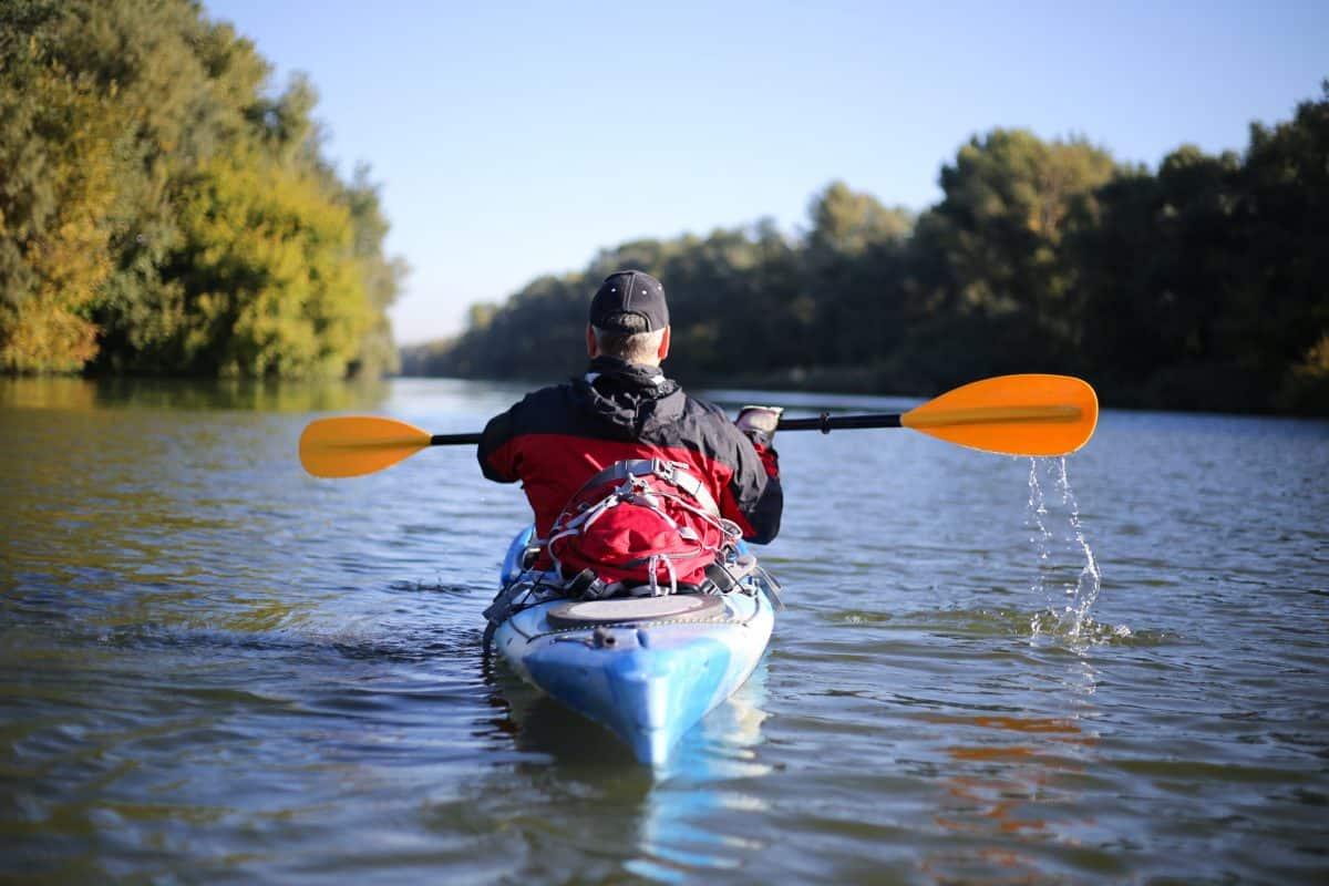 shot from behind of man in Sit-in kayak