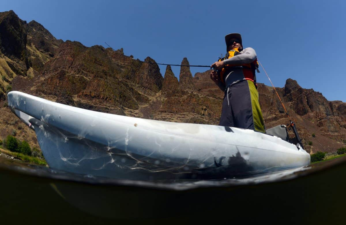 man fishing in kayak in beautiful landscape in Oregon with mountains and river