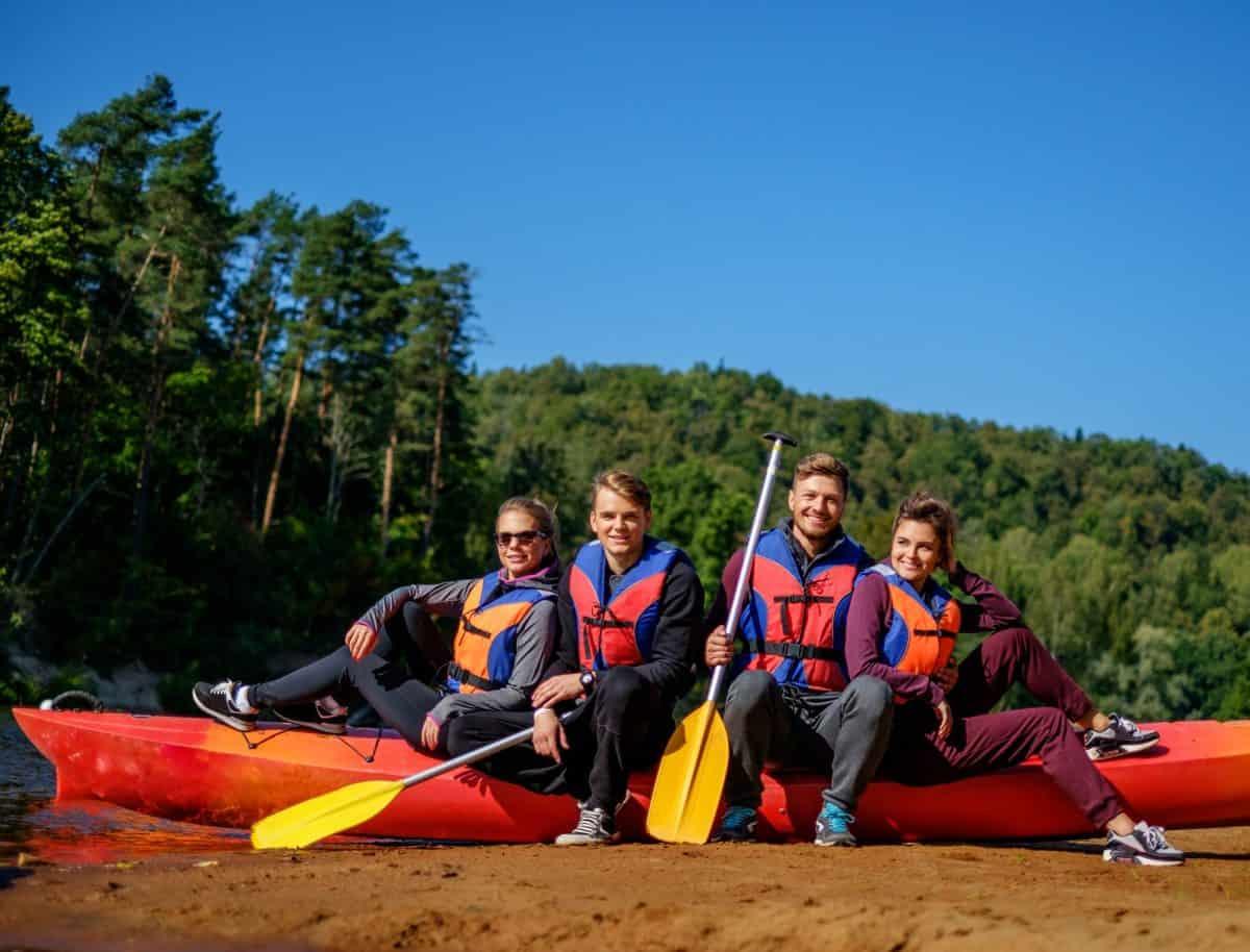 Group of people wearing life jackets near kayak