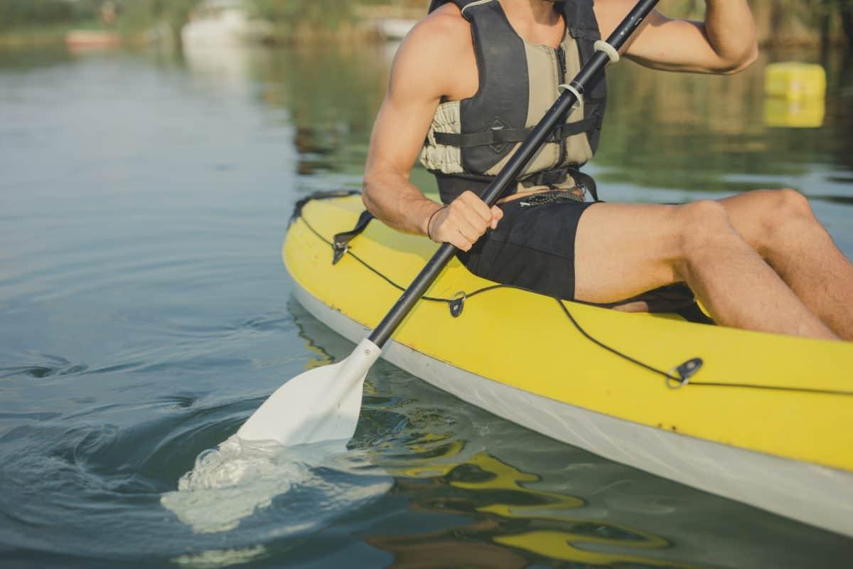 Unrecognisable man wearing life vest kayaking