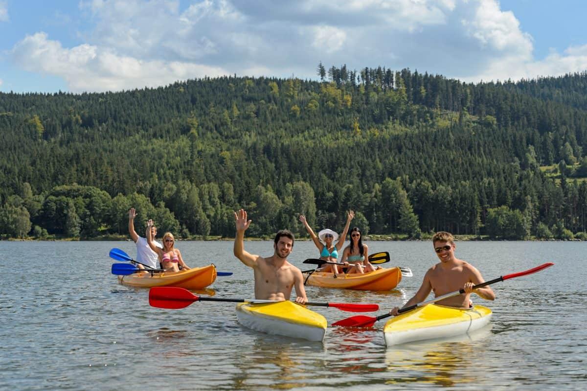 cheerful friends in kayaks summer