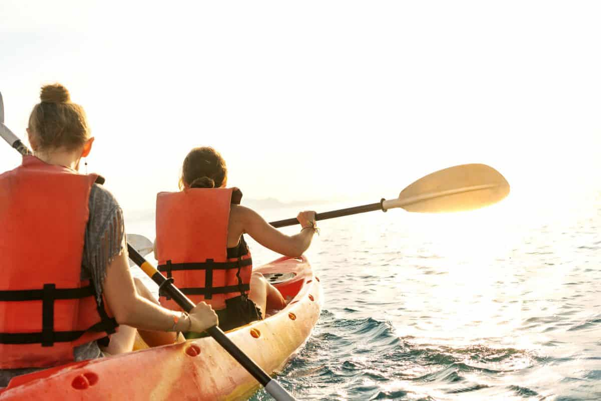 young couple kayaking on lake together and smiling at sunset