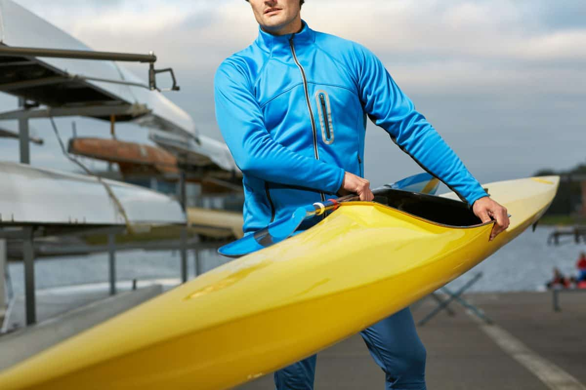 Male athlete in swimming sportswear carrying yellow kayak and paddle outdoors after training on the river,