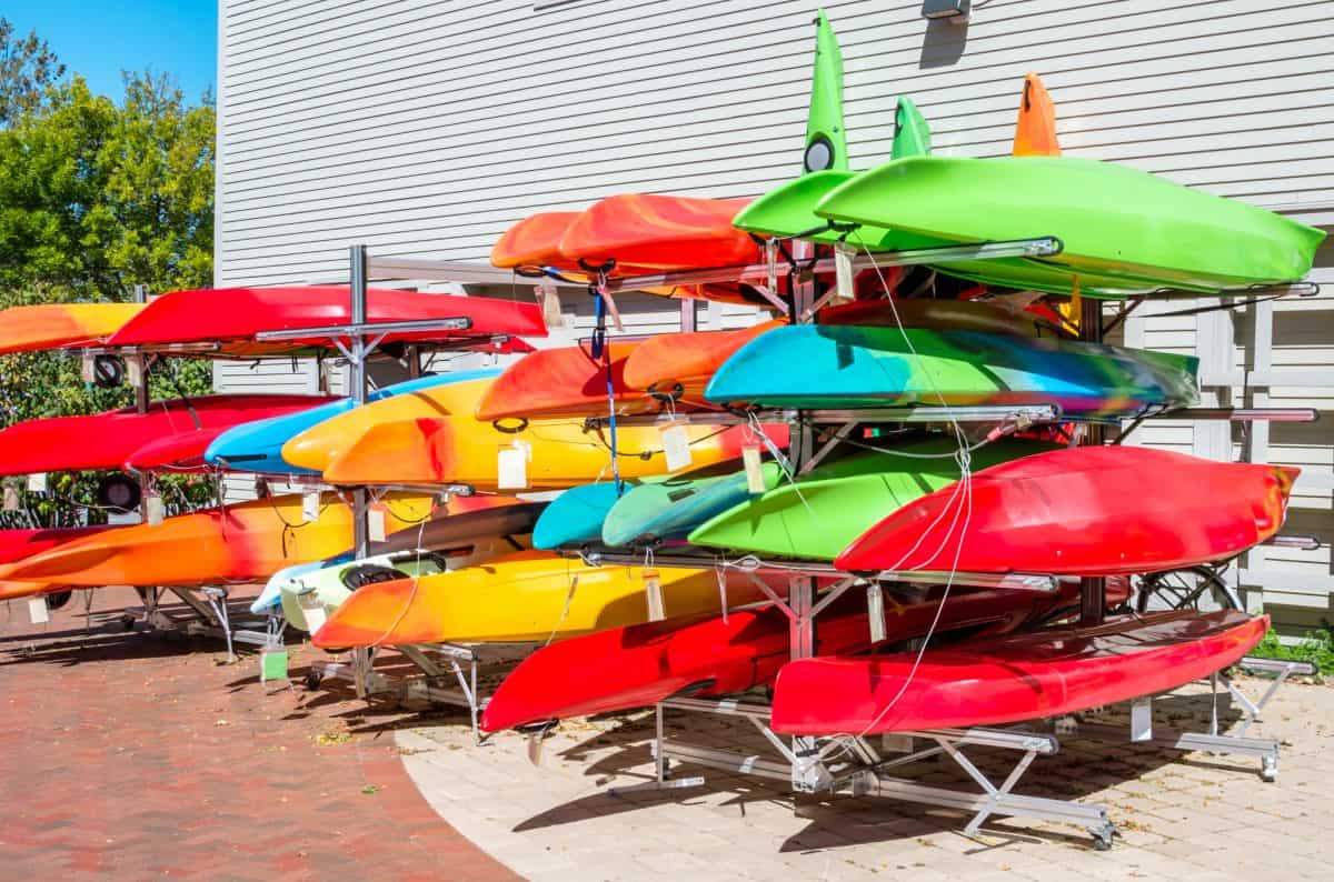 Colourful kayaks and canoes on sale outside an outdoor equipment store on a sunny autumn day