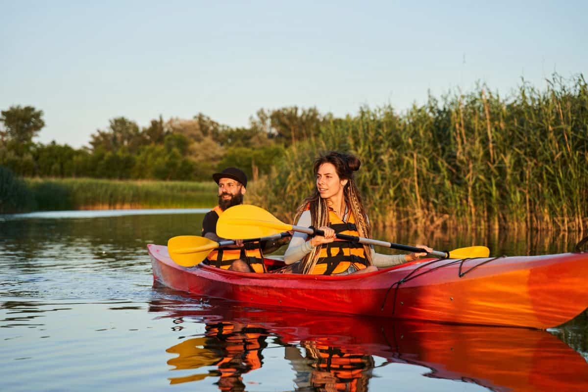 Couple of kayakers paddling during sunset