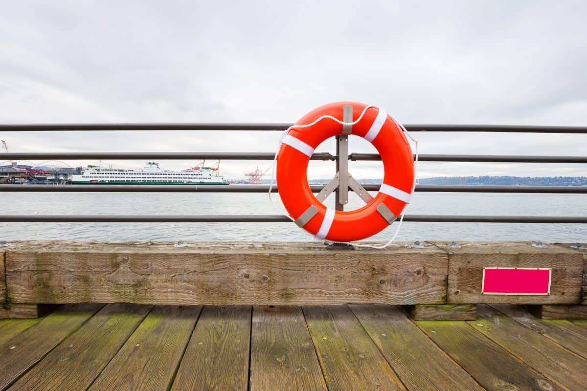 Orange buoy on railing by the sea