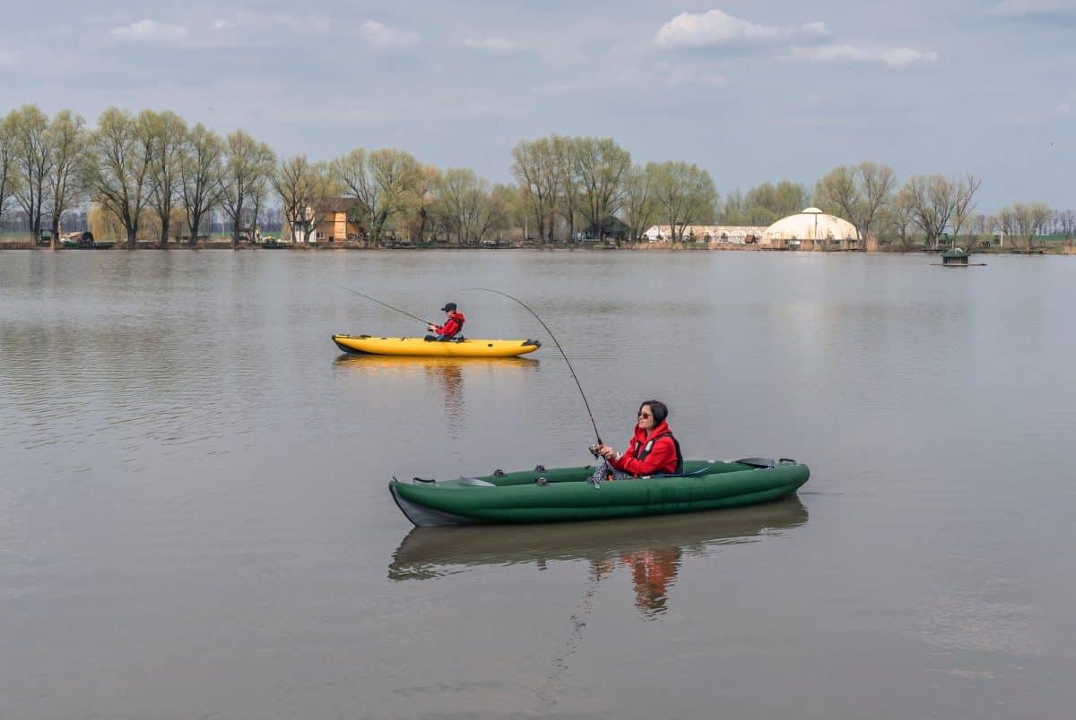 Kayak fishing at lake. Two fisherwomen on inflatable boats with fishing tackle.