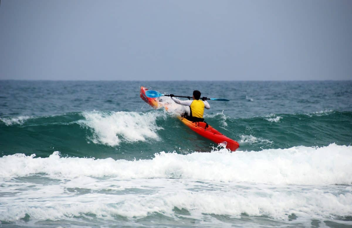 sea kayaker paddles towards to a wave