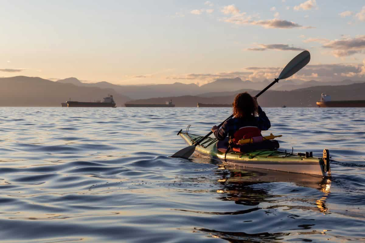 Girl Sea Kayaking during a vibrant sunny summer evening