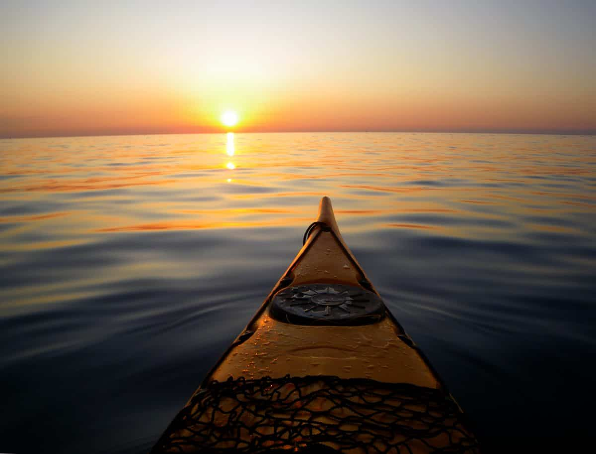 view from sea kayak at sunset