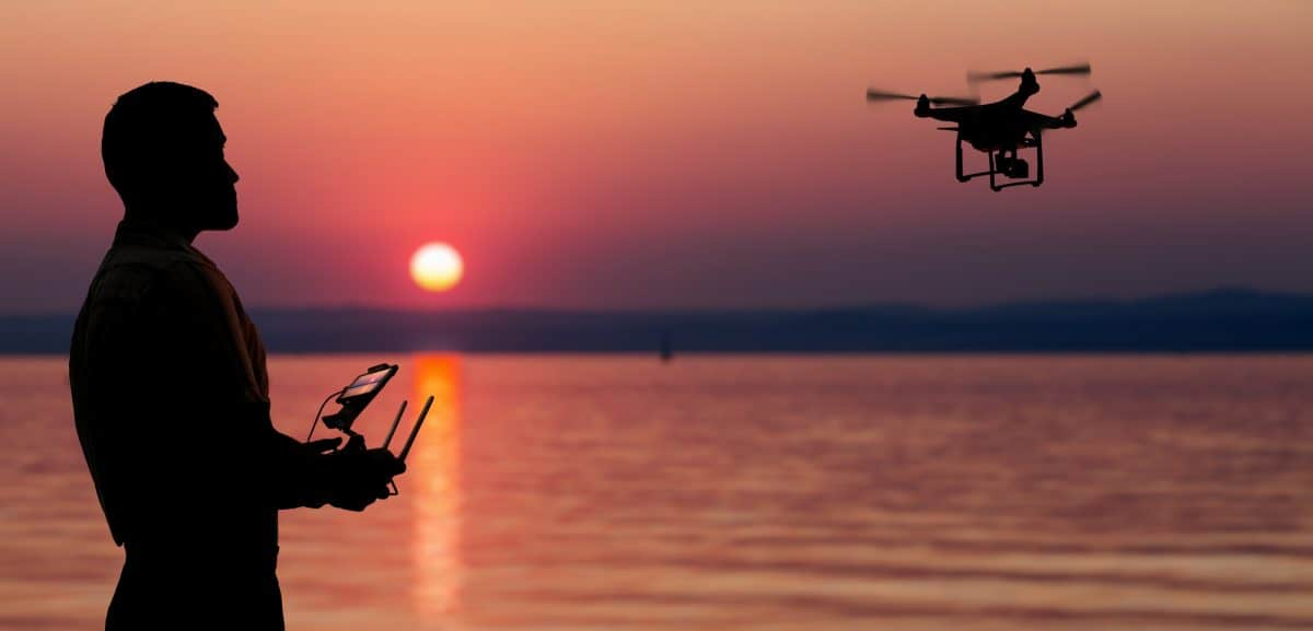 Man flying a fishing drone near seaside at the sunset